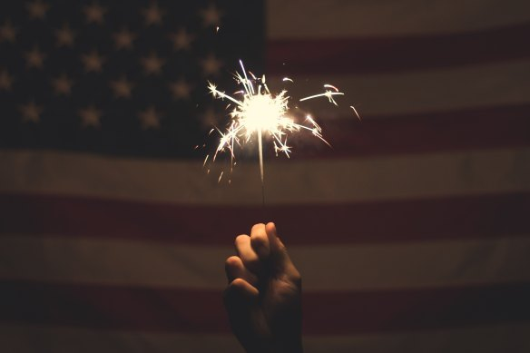 A hand holding a sparkler in front of the US flag.