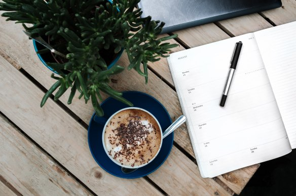 Pen on a planner next to a cappuccino.