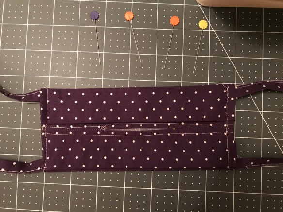 Completed purple and white polka dot face mask with inside filter pocket shown
